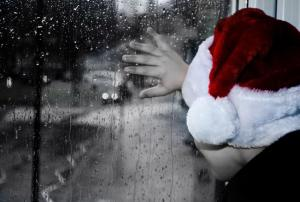 child-with-santa-hat-looking-out-window